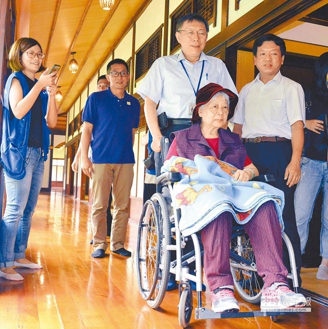 台北市長柯文哲,9日出席「台北市銀髮樂活行」記者會,親自為銀髮長者推著輪椅,讓長者輕鬆享受舒適的樂活環境 。(洪錫龍攝)