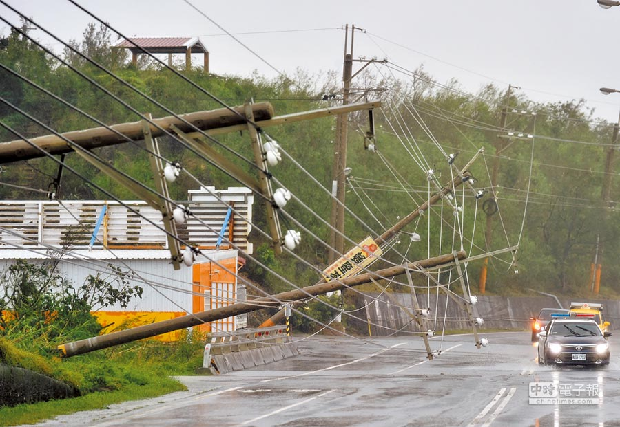 屏東一處高壓電纜線不敵強風肆虐橫倒在公路上。(法新社)