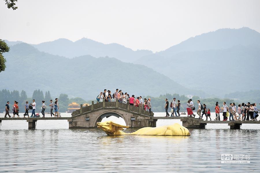 遊人走在浙江杭州西湖景區涌金橋上。(新華社)