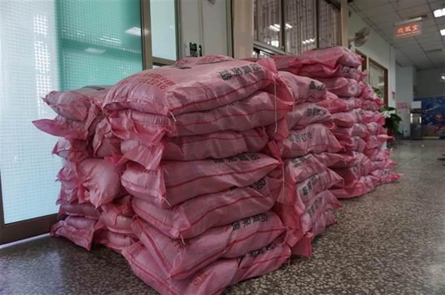 白米堆疊成山,老農廖德忠連存3年老農津貼,購買1萬斤白米助弱勢。(王文吉攝)