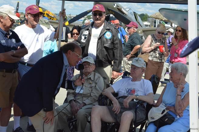 飛虎老兵們在漆有青天白日徽的P-40戰鬥機前接受訪問。(許劍虹攝)