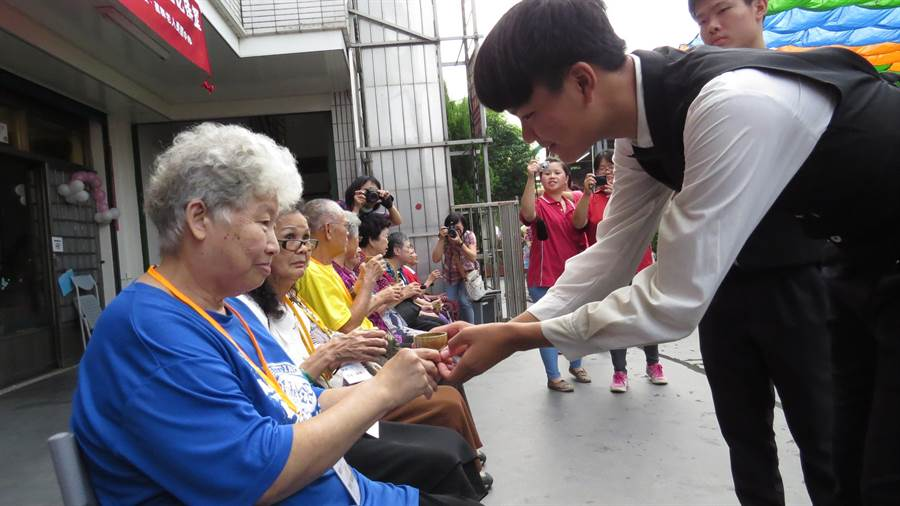 達德商工餐飲科學生為珍瑩老人養護中心的長輩奉茶。鐘武達攝。
