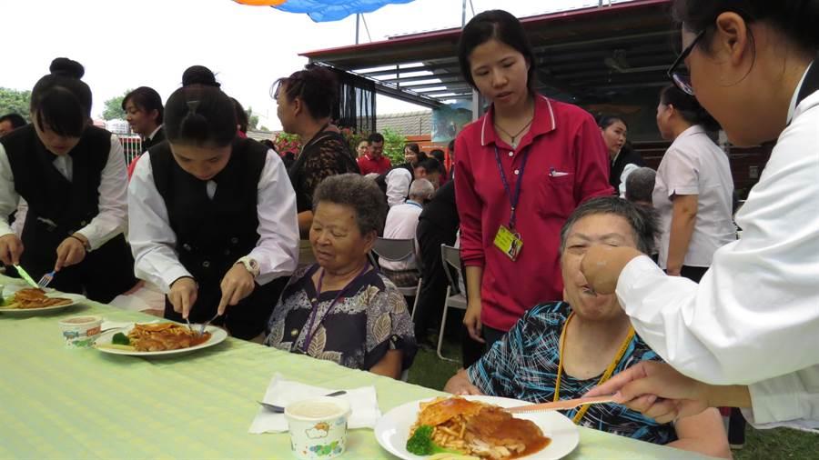 達德商工學生請老人家吃排餐,還親自餵食。鐘武達攝。
