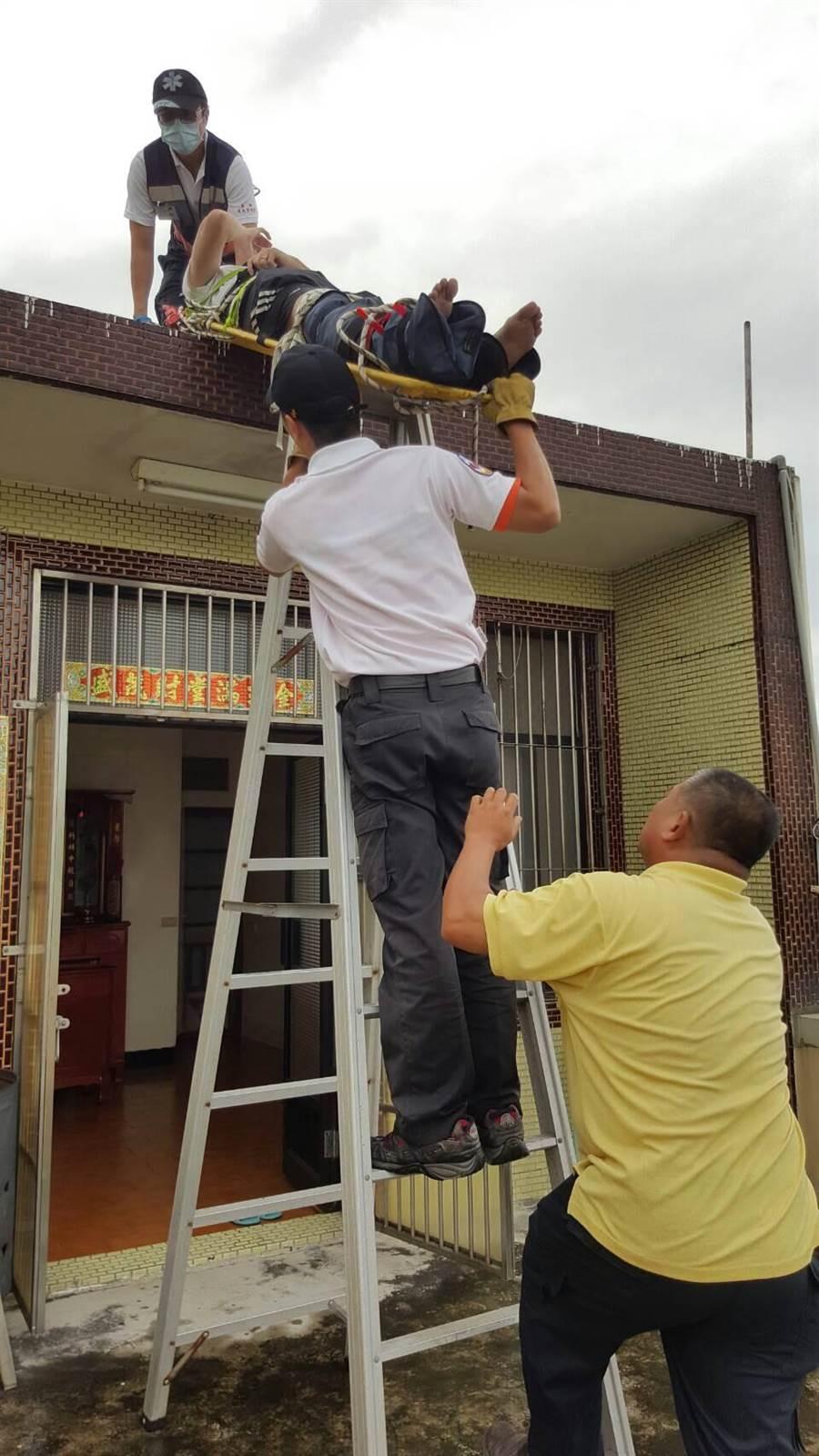 林男從5樓公寓跳至隔壁4樓屋頂露台,腳踝扭傷,救護人員費力將他救下。(林宏聰翻攝)