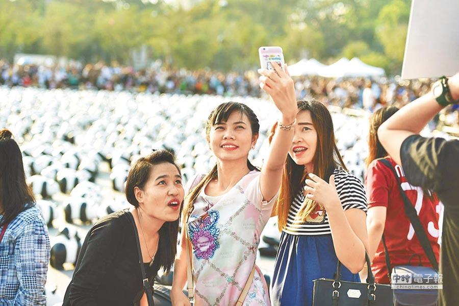 北京女孩觀看紙製大熊貓展時用手機自拍。(新華社)