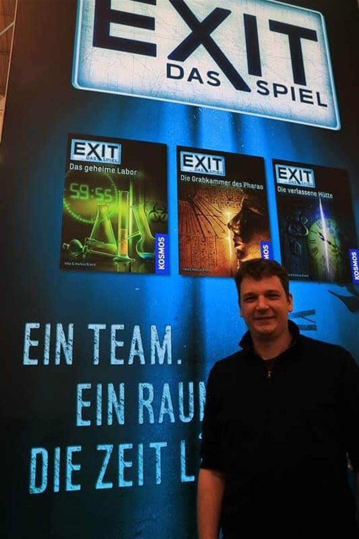 今年桌遊潮流是生存遊戲,圖為德國生存遊戲EXIT產品經理 Ralph Querfurth 和該公司個今年上市的德文遊戲。(紀蘊之/攝)