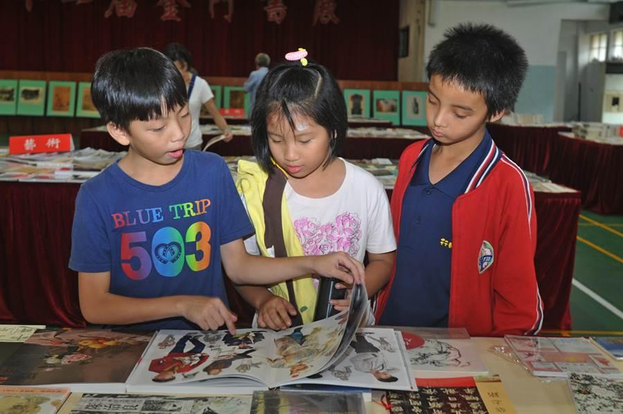 幾位小朋友翻閱圖畫冊,一起開心討論著。(李金生攝)