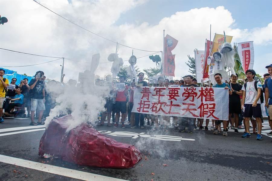 青年團體點燃道具肝裡的鞭炮,象徵青年勞工「爆肝」的現況。(杜宜諳攝)