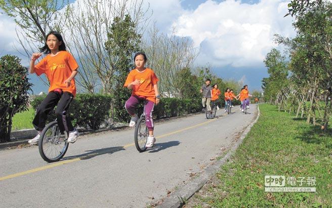 福原國小學生小心騎著獨輪車環繞大坡池一周,學生們笑著說「很累,但是很值得。」(本報系資料照片)
