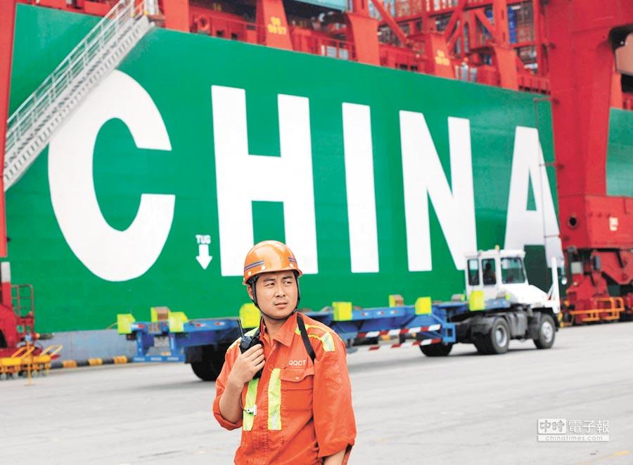 2015年7月15日,山東青島港外貿貨櫃碼頭,一名工人指揮貨櫃裝卸。(新華社)