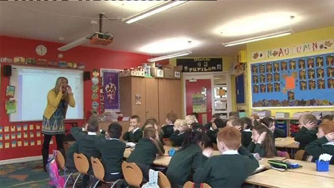 英國一位小學女老師弗拉納根(左)22年前曾喊出121.7分貝的世界紀錄,至今無人打破這個紀錄。不過,弗拉納根 說,她從未大吼學生。圖為弗拉納根和學生有趣互動。(圖截取自BBC新聞網)
