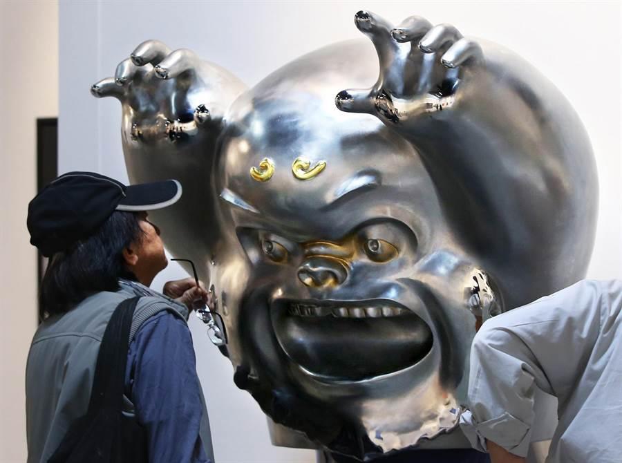 藝術家蔡尉成創作《膽小鬼》(中)不鏽鋼作品,「穿上勇氣,你也可以所向無敵」,吸引1位男子駐足觀賞。(王錦河攝)