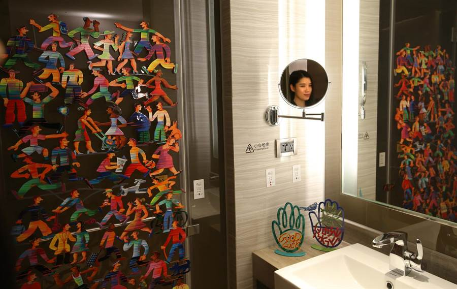 城市商旅真愛館共58間商務套房內展示各家藝廊的作品,連衛浴空間也充分利用,展示藝術家 David Gerstein 創作《Side Walk》不鏽鋼彩繪作品,倒映在鏡中。(王錦河攝)