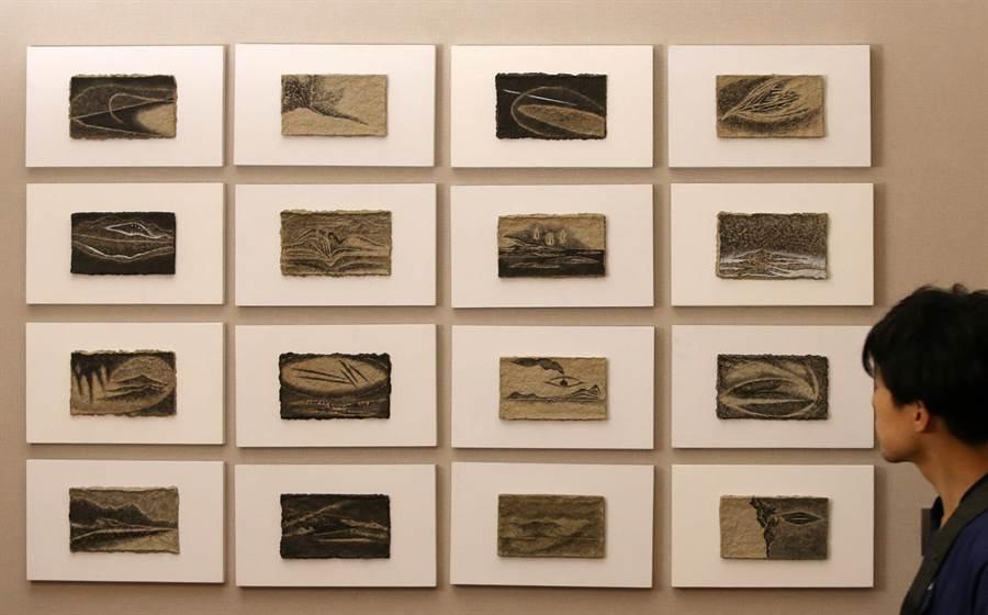 藝術家彭賢祥以紙漿和水墨創作《山水》系列作品,吸引1位男子觀賞。(王錦河攝)