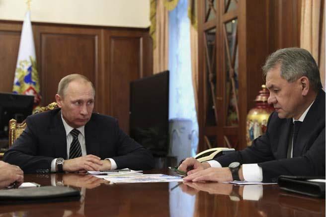 俄羅斯總統普丁29日在莫斯科聽取防長紹伊古關於俄軍在敍利亞的軍情。普丁宣布在敍利亞將停火。(圖/美聯社)
