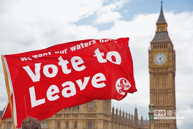 英國去年6月23日通過脫歐公投。圖為公投前飄揚在倫敦國會大廈前的宣傳旗幟,呼籲人民「票投脫歐」。(美聯社)