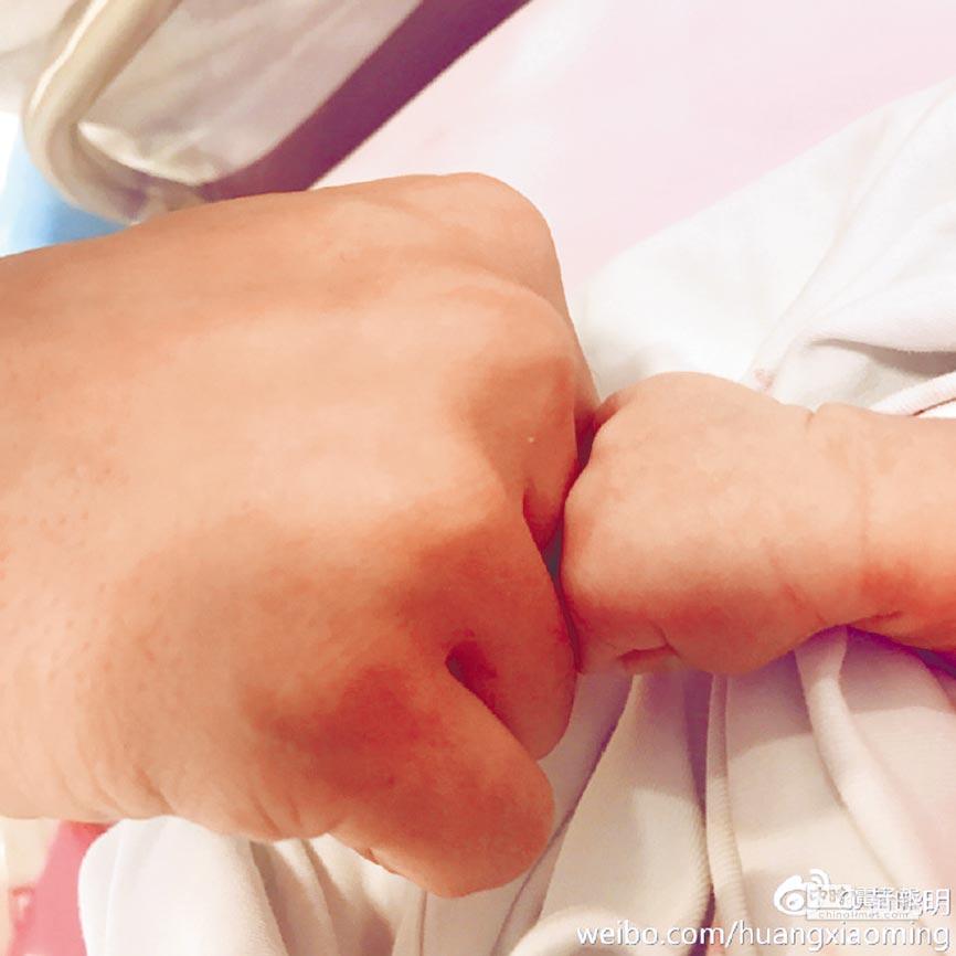 黃曉明和兒子「小海綿」很Man地擊拳。(取材自微博)