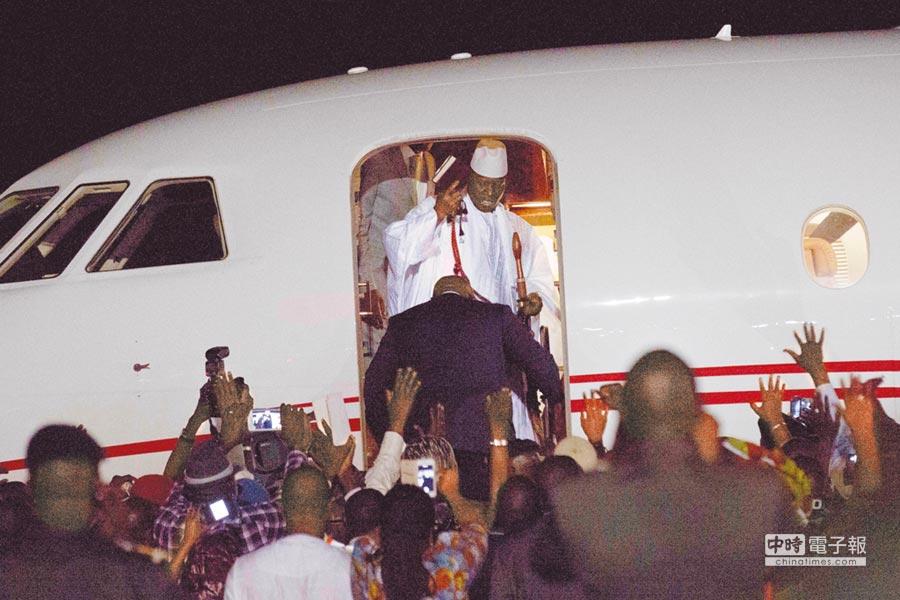 甘比亞總統賈梅終於交出統治長達22年的政權,21日在首都班竹機場準備搭機出亡時,向支持者揮別。(美聯社)