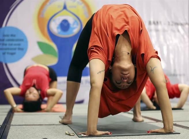 2015年6月21日,聯合國首次將這一天訂為國際瑜珈日,菲律賓馬尼拉當天舉行慶祝活動,許多瑜珈愛好者一起共襄盛舉。圖中的瑜珈動作為輪式,和駱駝式一樣是往後伸展的動作,但是難度更高。(圖/美聯社)