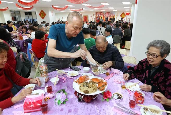 高雄鳳山新城除夕圍爐席開70桌,許多眷村住戶全家一同參與並幫父母盛菜,共度除夕夜。(王錦河攝)