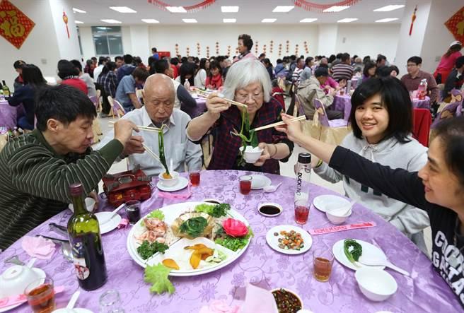 高雄鳳山新城除夕圍爐席開70桌,許多眷村住戶全家一同參與並幫父母夾菜,共度除夕夜。(王錦河攝)