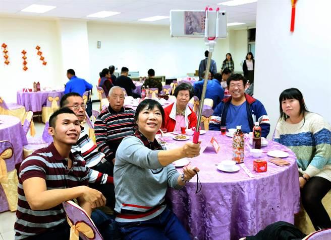 高雄鳳山新城除夕圍爐席開70桌,其中1家人合影留念。(王錦河攝)
