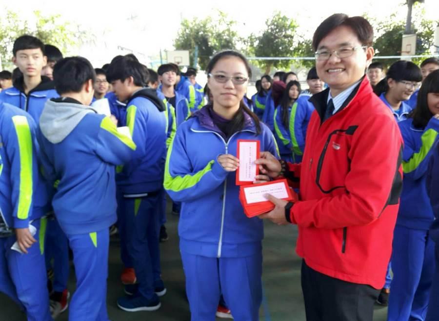 溪陽國中校長黃森明開學日贈送學生一元紅包以及勵志籤詩。鐘武達攝。