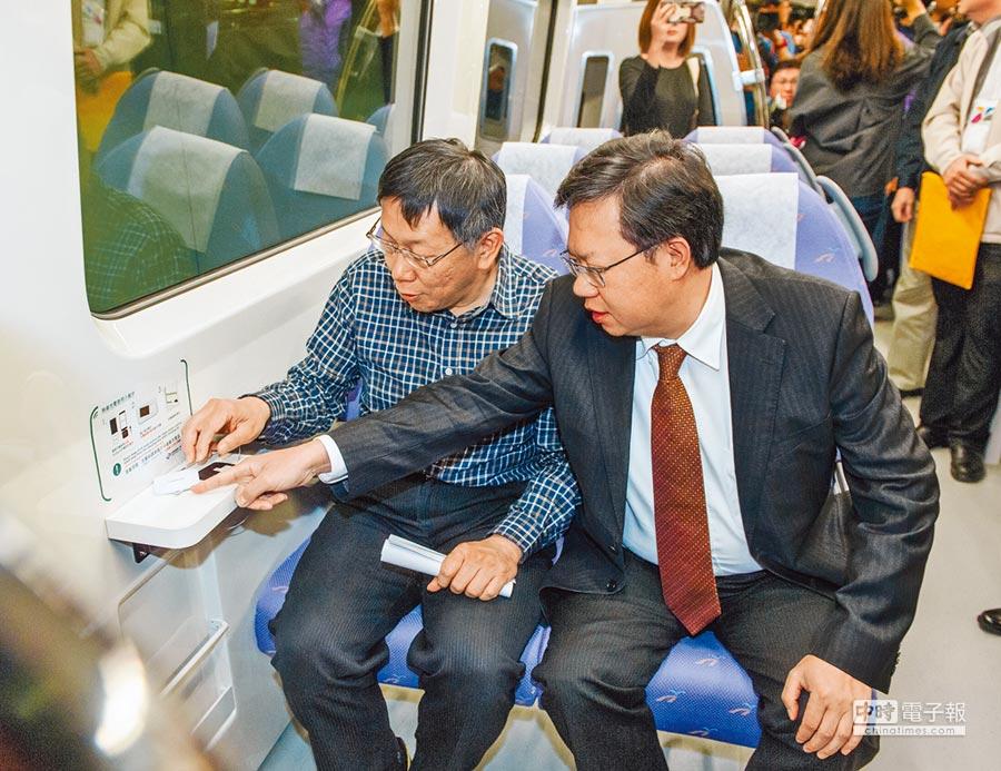 台北市長柯文哲(左)昨在桃園市長鄭文燦(右)陪同下試乘機場捷運,列車上設置的手機無線充電設備,讓柯文哲花了不少時間研究。