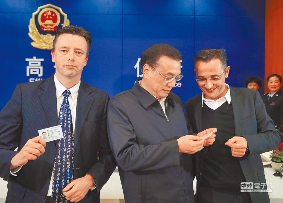2015年11月25日,大陸國務院總理李克強(中)在陸家嘴片區行政服務中心境外人員永久居留證辦理窗口,現場見證了兩位國外引進人才領取「中國綠卡」。(中新社)