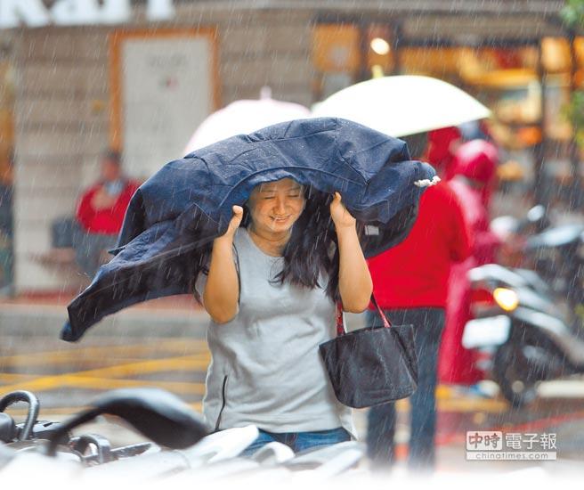 台北地區昨天中午出現陣雨,讓路過民眾措手不及。(陳怡誠攝)