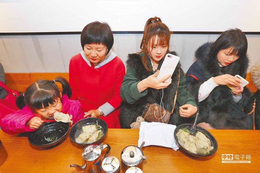 上海人氣美食「夢花街」餛飩19日在中華路重新開業,前來品嘗的民眾在門前排起了長隊(左圖),幸運入座的食客,有的拿起手機拍照、有的大快朵頤(右圖)。(CFP)
