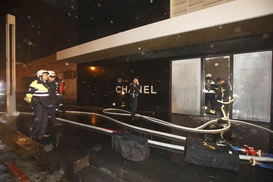 台北晶華酒店半夜火警,消防人員擊破精品店玻璃進入灌救。(杜宜諳攝)