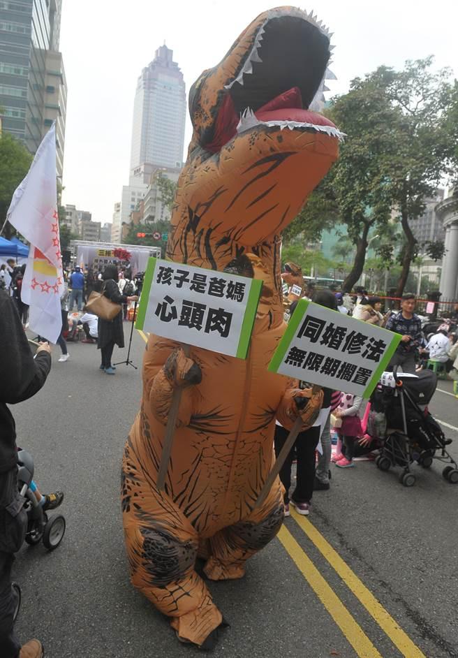反同婚團體「滿天星素人連線」4日舉辦「百萬大叔站起來-陽春麵大會師」活動,現場出動大型恐龍道具,拿著訴求標語四處遊走。(季志翔攝)