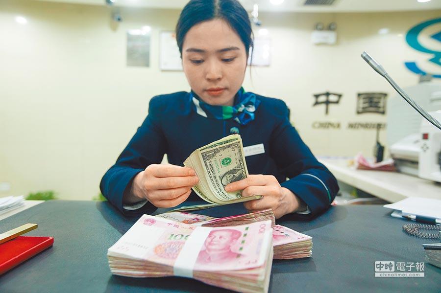 6日,山西太原銀行工作人員正在清點貨幣。(中新社)