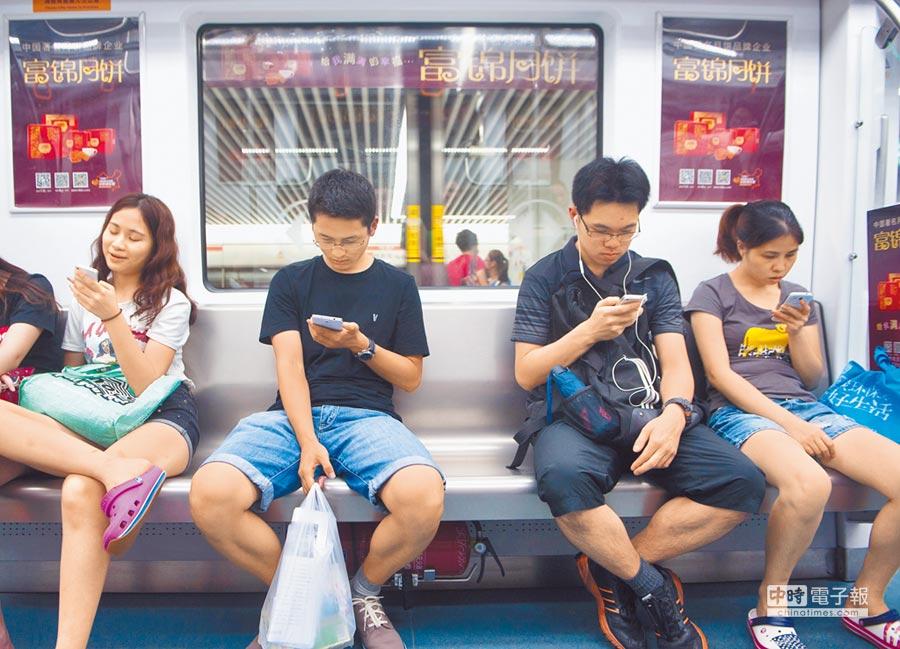 大陸APP也加入山寨行列。圖為民眾搭乘深圳地鐵時使用手機。(新華社資料照片)