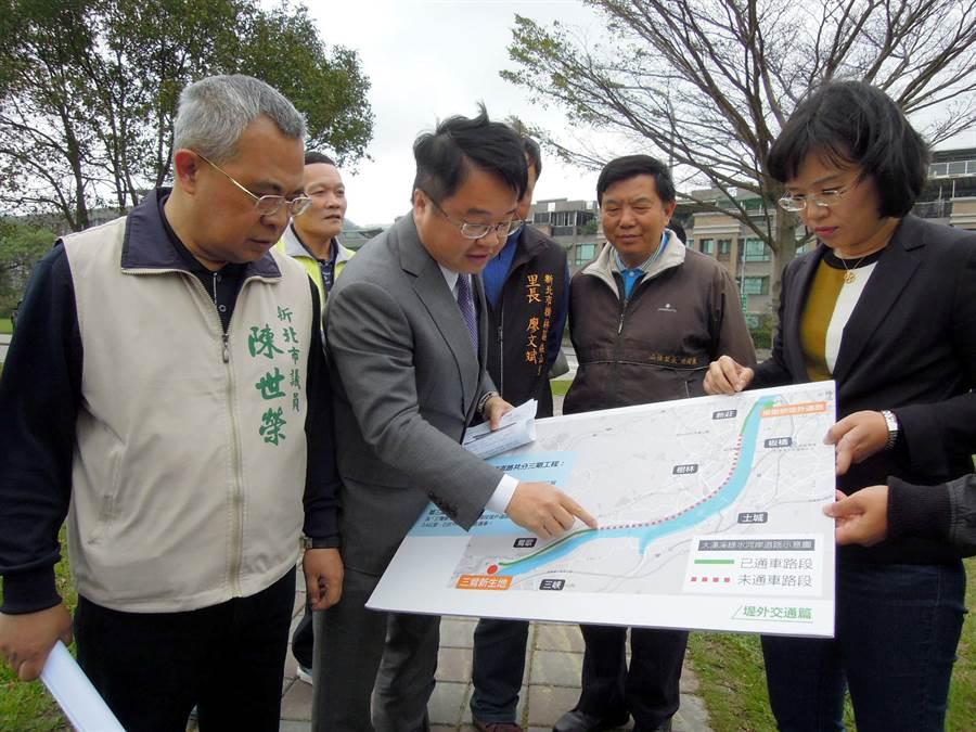 立委蘇巧慧、吳秉叡及市議員陳世榮(右至左)拿著工程示意圖,呼籲盡速闢建新莊西盛到樹林山佳的大漢溪左岸河岸道路。(陳俊雄攝)