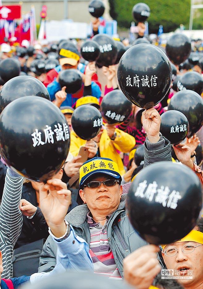 抗議年金改革,民眾吹起黑色氣球後再刺破,諷刺「政府誠信」破滅。(本報資料照片)