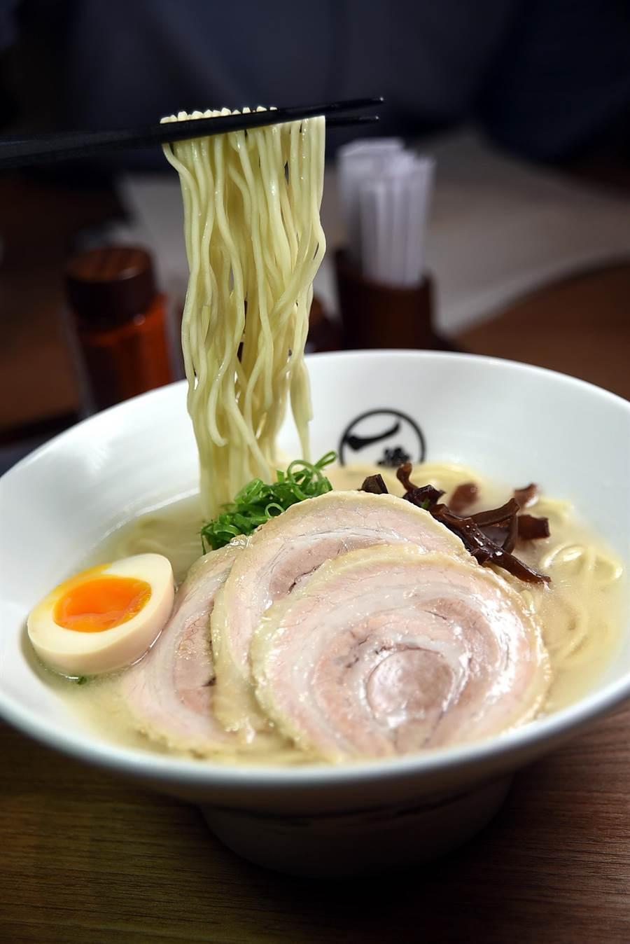 〈一燈白豚拉麵〉的湯頭是用豬骨熬煮14小時,湯色乳白、喝後會黏嘴,代表湯內質富含膠質。(圖/姚舜攝)