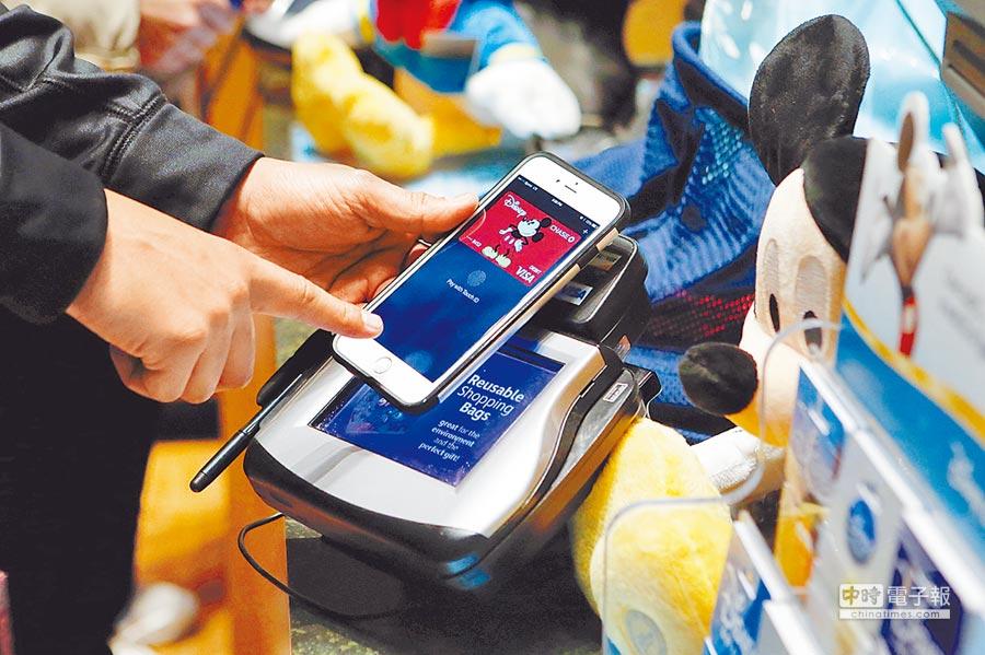 行動支付開跑  3月29日早上7點起,全台民眾只要拿iPhone6以上的手機,將信用卡透過「錢包App」掃入設備中,即可在各大通路直接消費付款。圖為一名客人在迪士尼專賣店,使用Apple Pay購物。(美聯社)