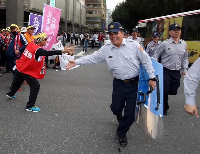 台灣警消聯盟發起軍公教「遍地開花」抗議遊行,大量警方在各重要機關警戒,員警移防時和陳情聯盟成員擊掌加油。(陳君瑋攝)