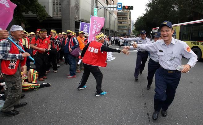 台灣警消聯盟發起軍公教「遍地開花」抗議遊行,大量警方在各重要機關警戒,員警移防時和聯盟成員擊掌加油更比出大拇指讚。(陳君瑋攝)