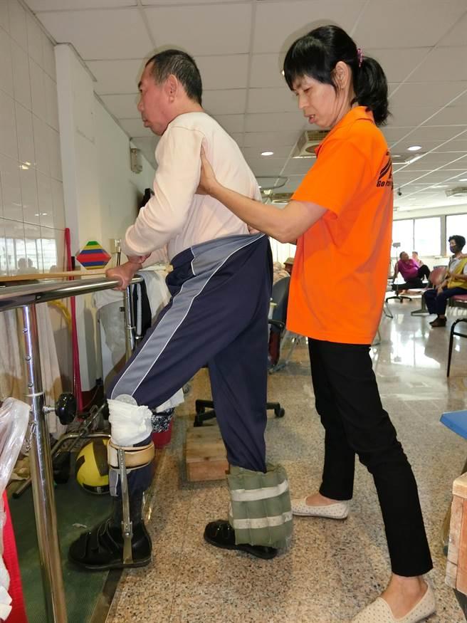 照顧秘書羅素蓉陪伴服務對象洪大哥複習復健運動。(弘道提供)