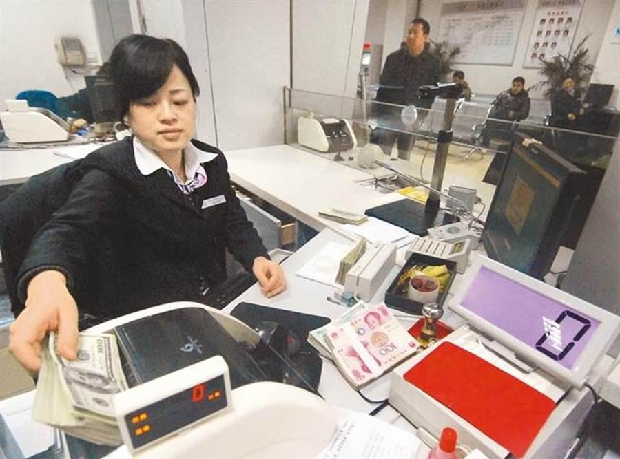 中國工商銀行行員在清點美元及人民幣。(資料照/新華社)
