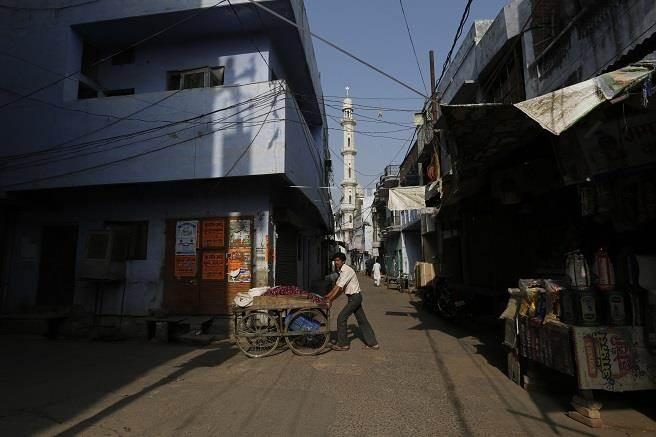 一個印度攤販正從巷弄內經過。(圖/美聯社)