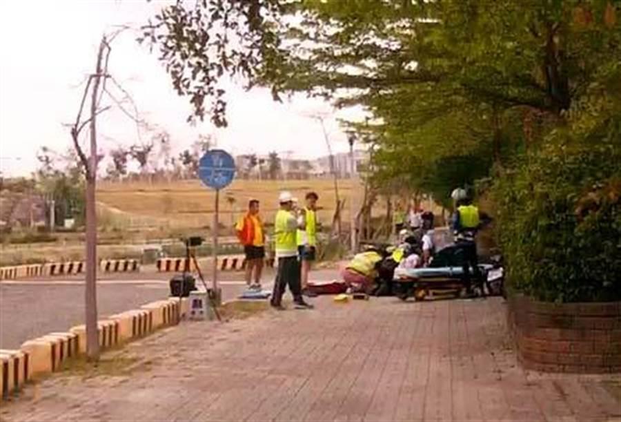 張姓男子參加路跑昏倒,現場跑者協助救護人員急救。(曹明正翻攝)