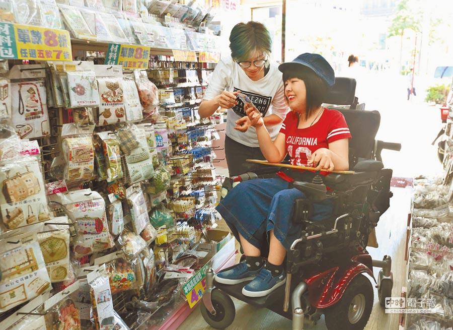 街頭藝人阿真(右)罹患先天性肌肉萎縮症,申請社會局個人助理方案,幫助她生活自立。(王錦河攝)