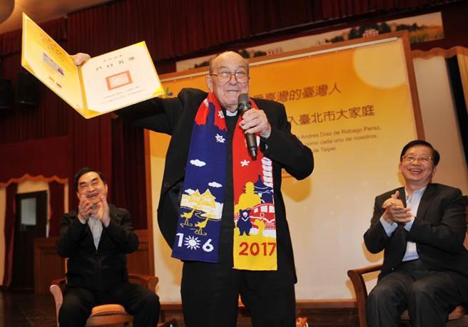 賴甘霖神父(前)13日獲得歸化國籍許可證書與身分證,他開心的拿起來展示。(劉宗龍攝)