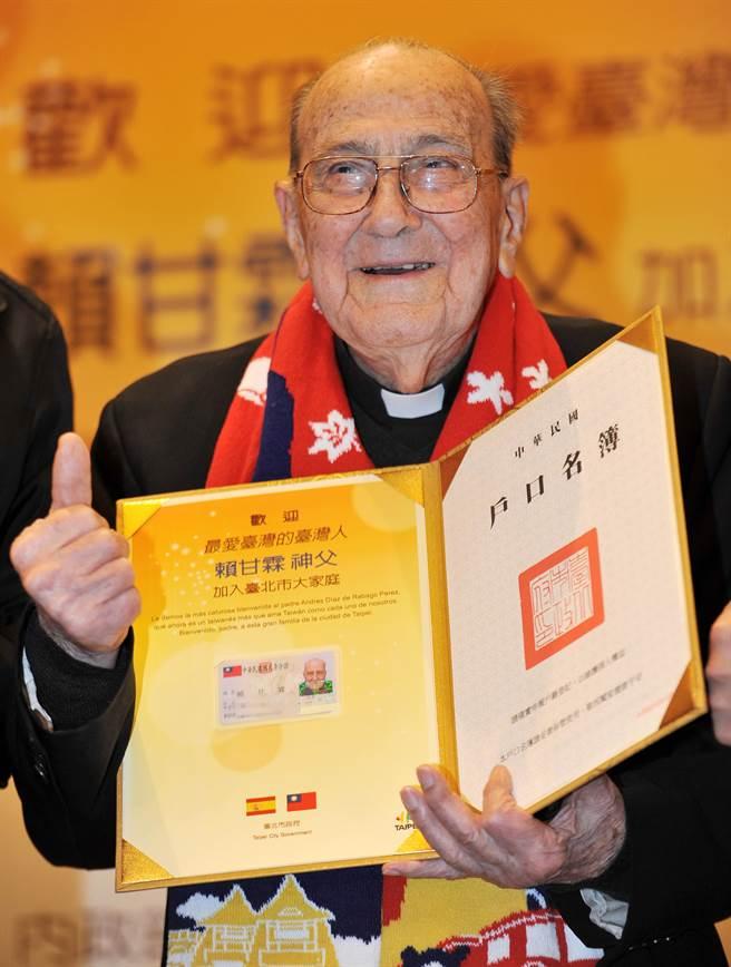 賴甘霖神父(見圖)13日獲得歸化國籍許可證書與身分證,他開心的拿著展示。(劉宗龍攝)