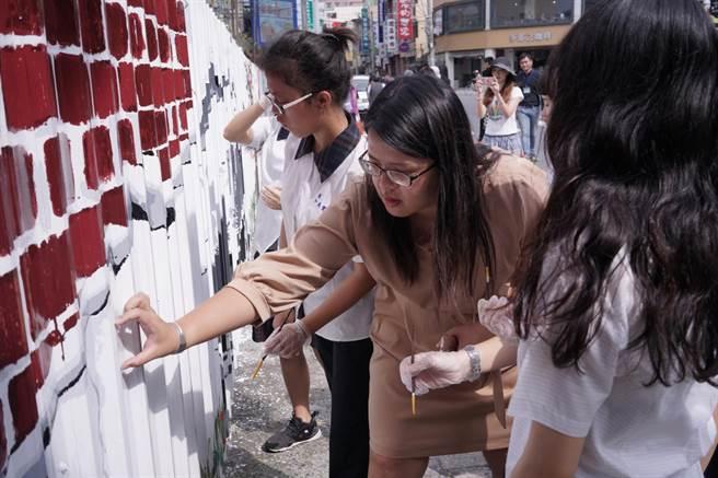 國立和美實驗學校師生今天上午在縣文化局號召邀請下,前來為和美街長宿舍的鐵皮圍籬進行主題彩繪。(謝瓊雲翻攝)