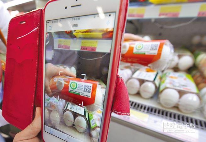 消費者在賣場選購雞蛋時,利用手機掃描包裝雞蛋的QR code檢視生產履歷,確保安全。(陳怡誠攝)